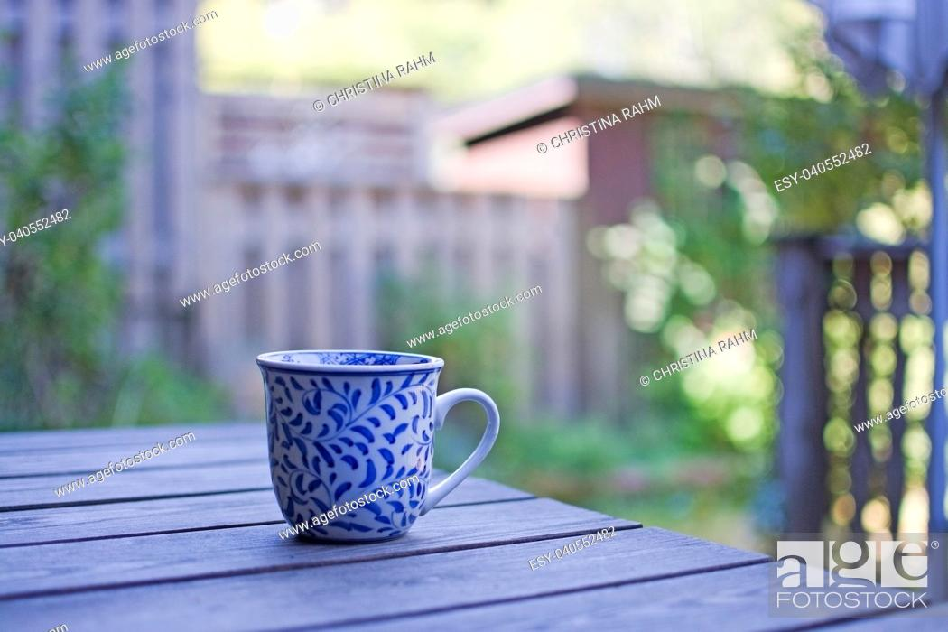 Stock Photo: Mug in blue pattern on wooden table outdoors in the shade in a garden.