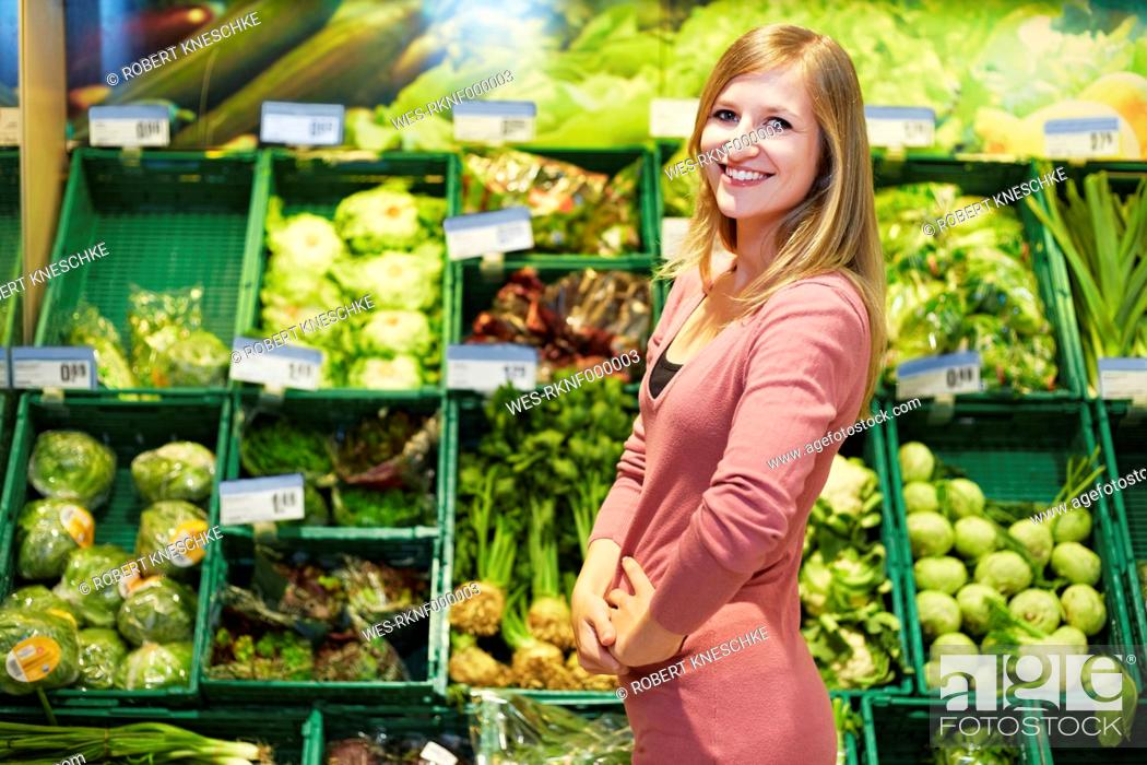Stock Photo: Germany, Cologne, Young woman in supermarket, smiling, portrait.