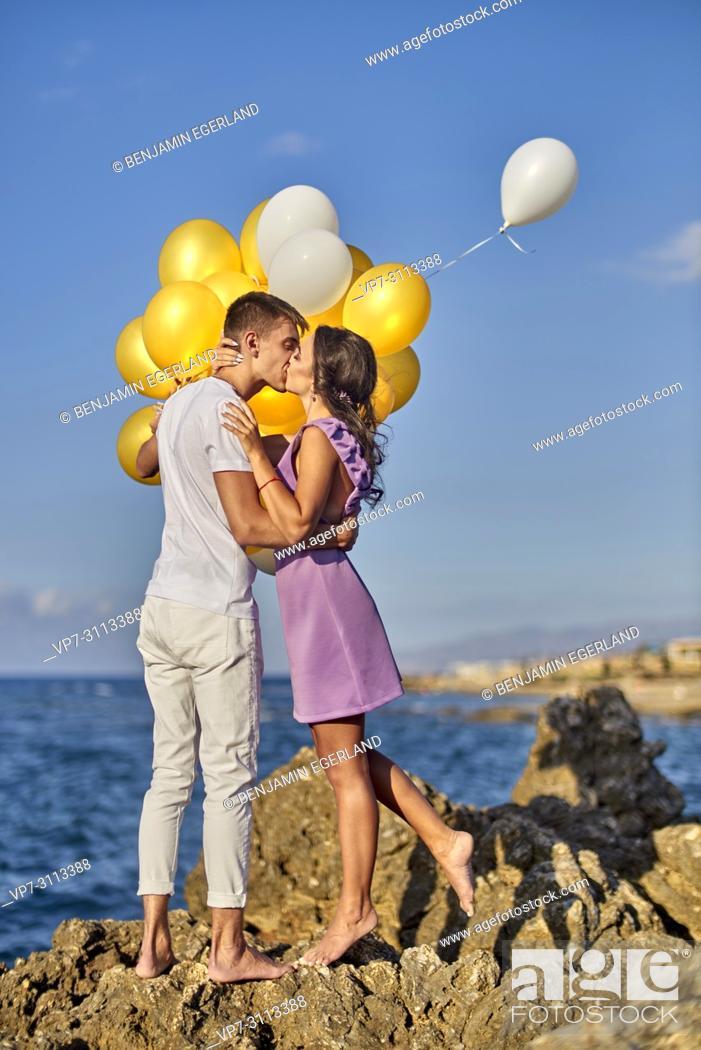 Stock Photo: romantic couple kissing, balloons, seaside.