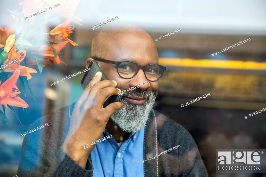Stock Photo: Portrait of smiling man on the phone behind windowpane.