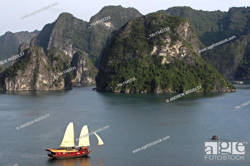 Stock Photo: Cruising junk with sails hoisted Halong Bay Vietnam.