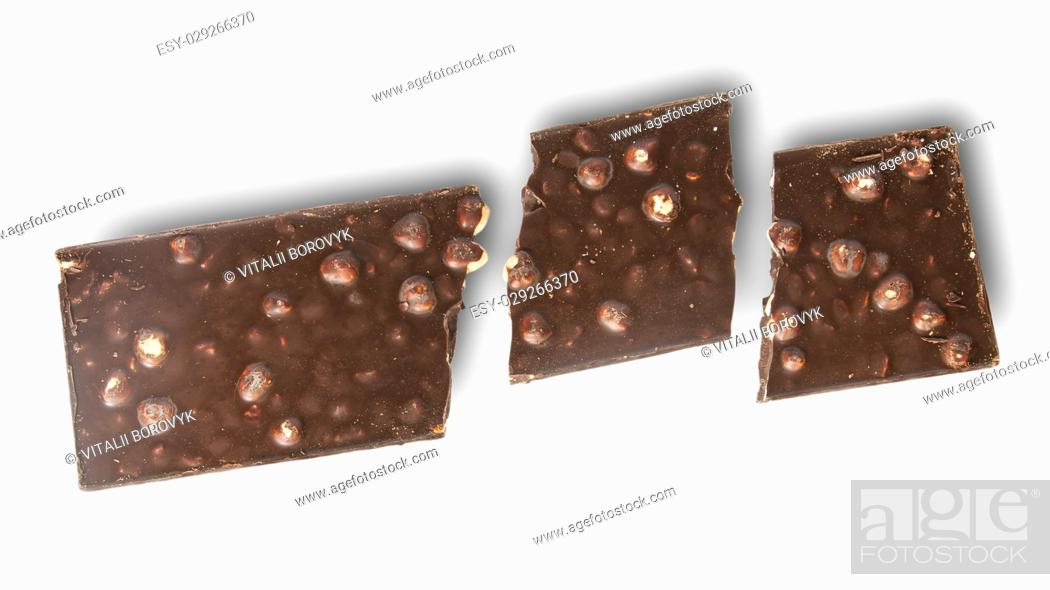 Broken Tiles Of Dark Chocolate With Whole Hazelnuts Isolated