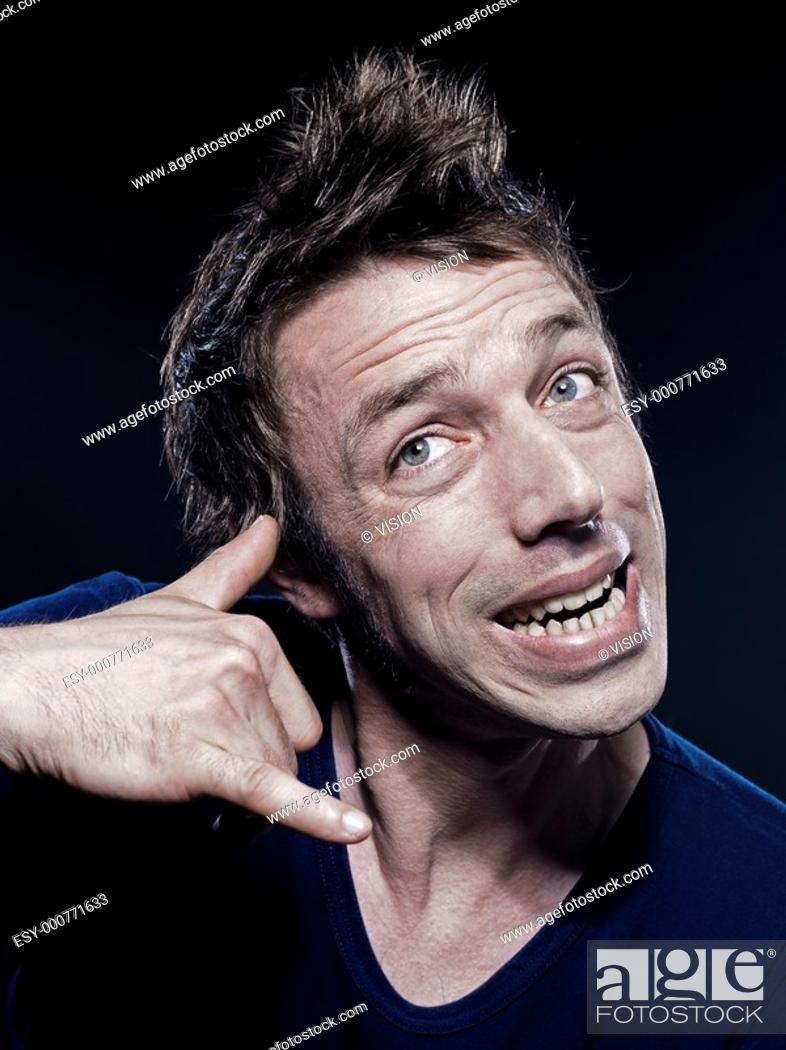 Stock Photo: studio portrait on black background of a funny expressive caucasian man phone hand sign.