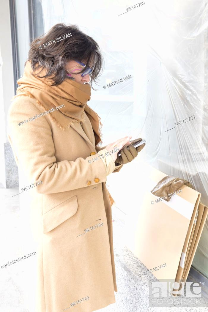 Stock Photo: Woman with Overcoat and Scarf Using Smart Phone.