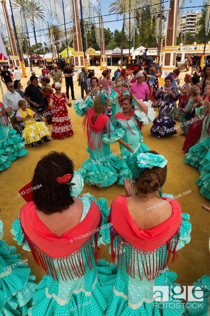 Stock Photo: Women wearing beautifully coloured gypsy dresses perform traditional Andalusian dances at the Feria del Caballo (Horse Fair) in Jerez de la Frontera.