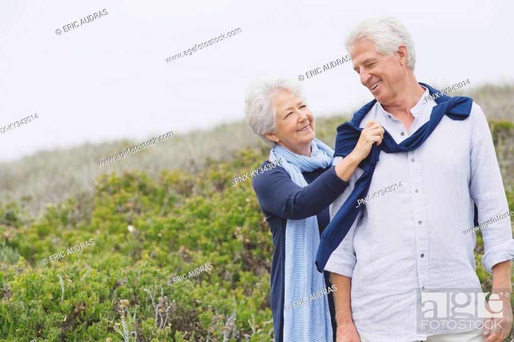Stock Photo: Senior woman putting sweater on husband's shoulder on the beach.