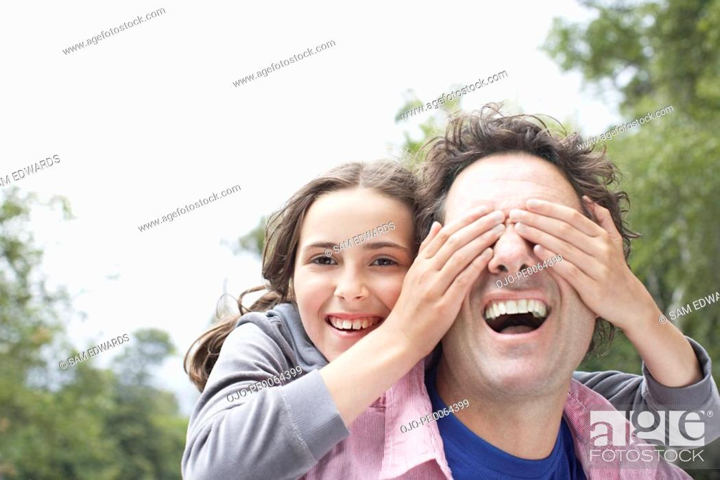 Stock Photo: Daughter covering fathers eyes.