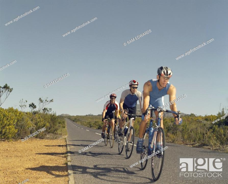 Stock Photo: Three bikers riding down the road.