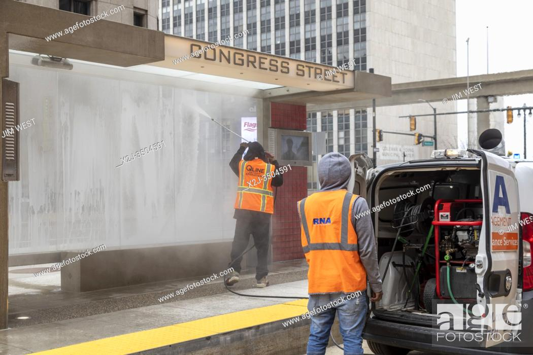 Stock Photo: Detroit, Michigan USA - 30 March 2020 - Workers disinfect a mass transit shelter in downtown Detroit.