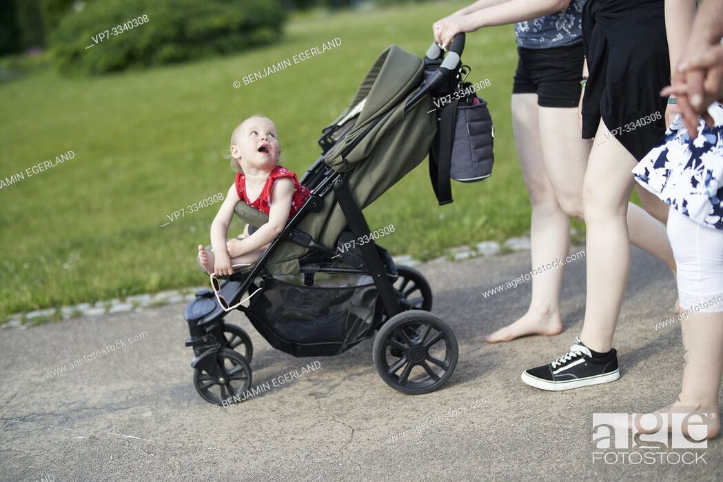 Stock Photo: communicative attentive baby toddler child in buggy looking backwards curiously at mother, walking in park.