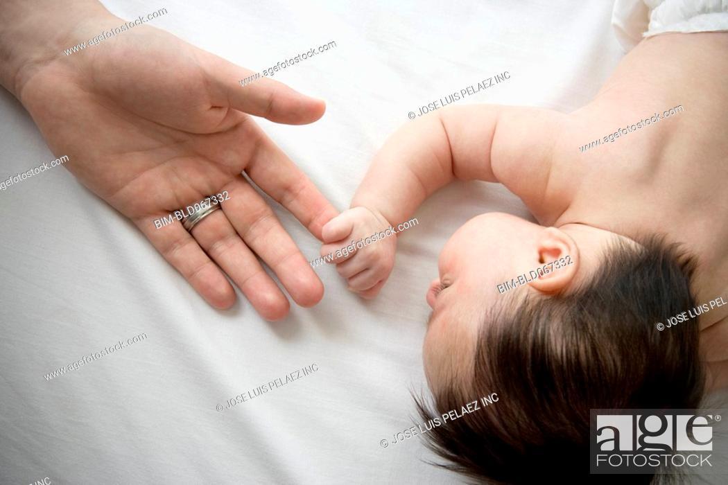 Stock Photo: Hispanic father holding tiny newbornÕs hand.