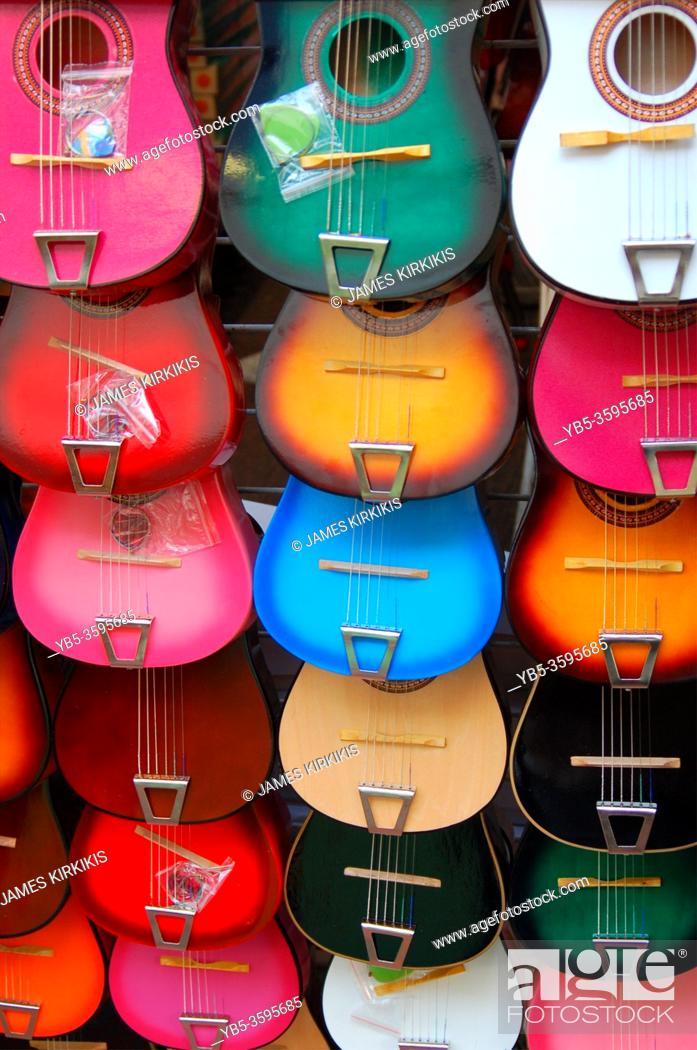 Stock Photo: Miniature guitars hang in a vendorâ. . s kiosk at El Pueblo Marketplace in Los Angeles.