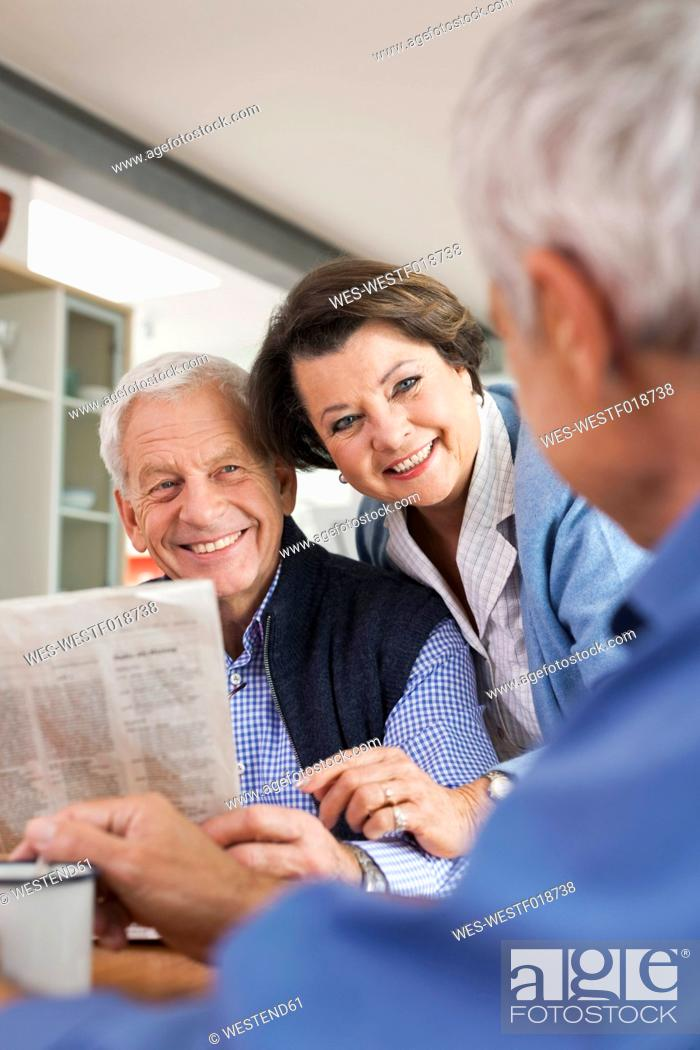 Stock Photo: Germany, Leipzig, Senior man reading newspaper, man and woman smiling.