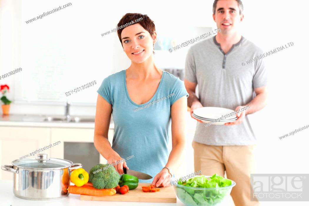 Stock Photo: Smiling Couple preparing lunch in a kitchen.
