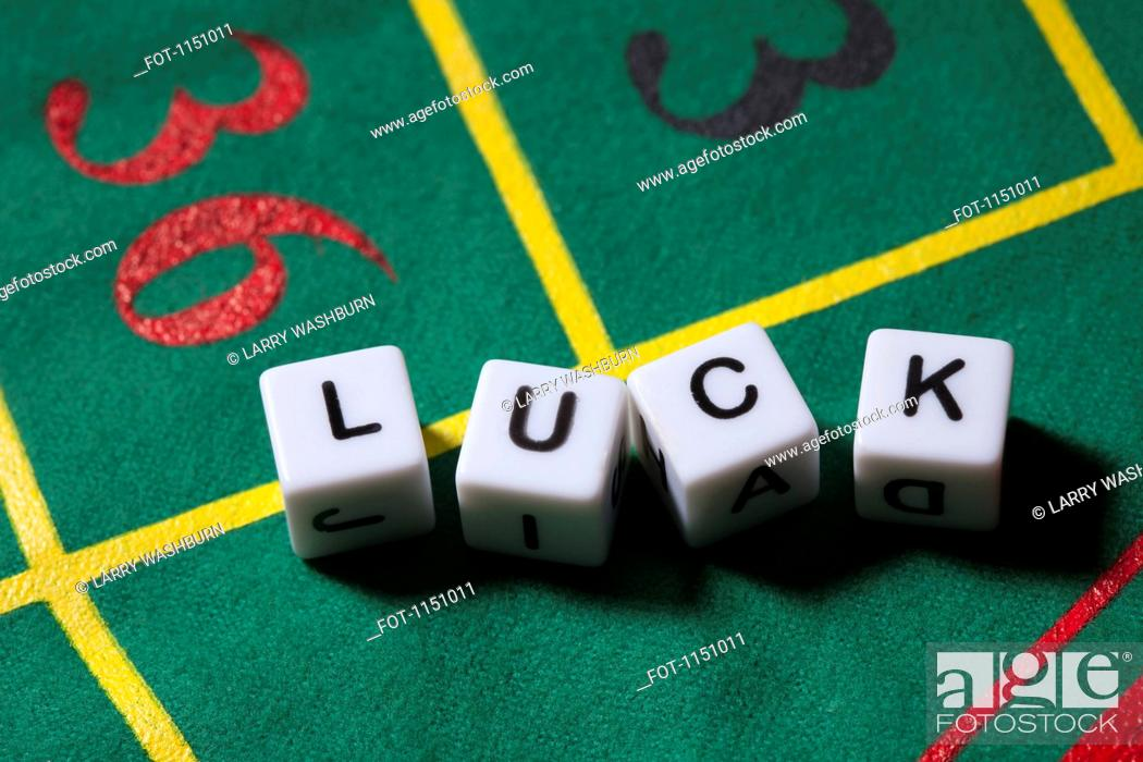 Stock Photo: Dice on a gambling table spelling the word LUCK.