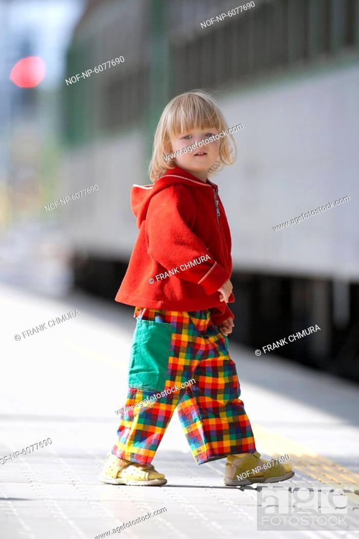 Stock Photo: Boy with long blond hair watching trains on railway platform.