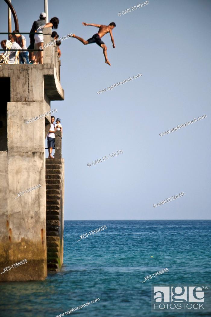 Stock Photo: Man jumping from the dock, Porto santo, Madeira.