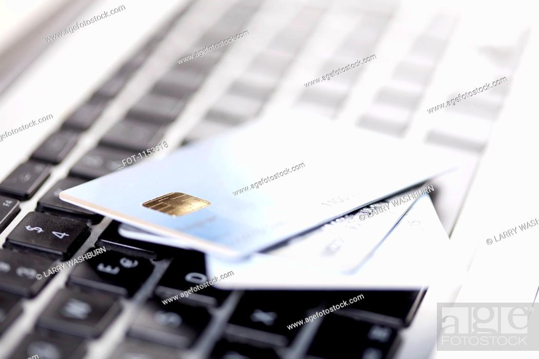 Stock Photo: Three credit cards lying on a laptop keyboard.
