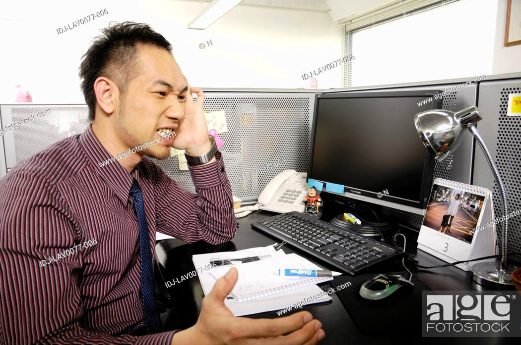 Stock Photo: Businessman looking frustrated in an office.