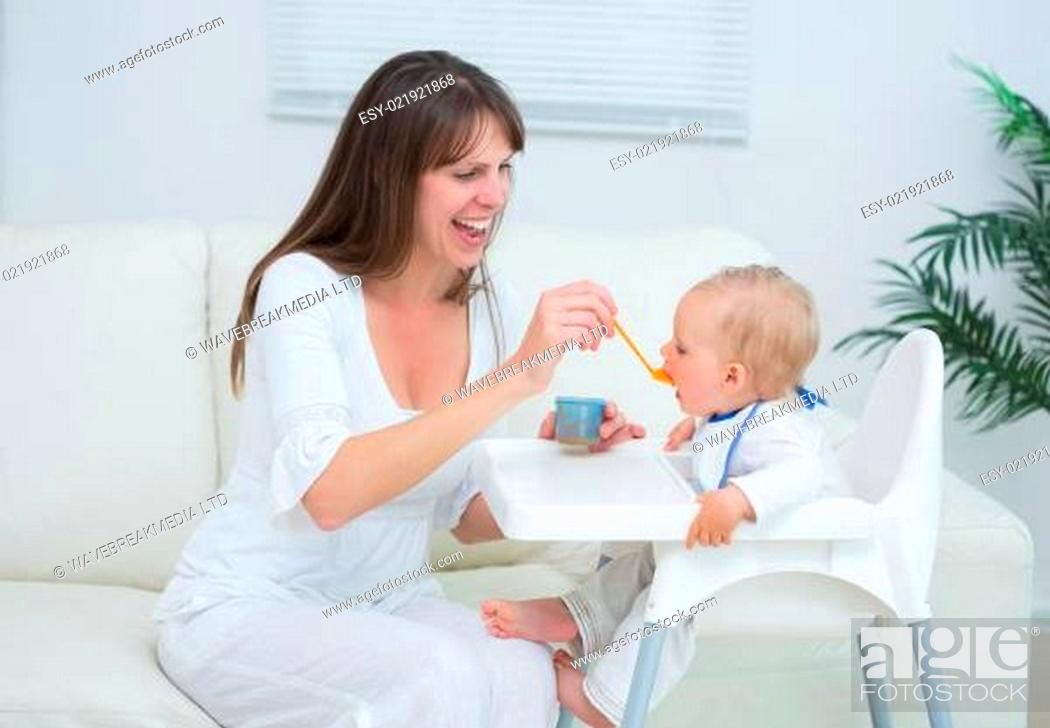 Stock Photo: Mother sitting in a sofa while feeding a baby in living room.