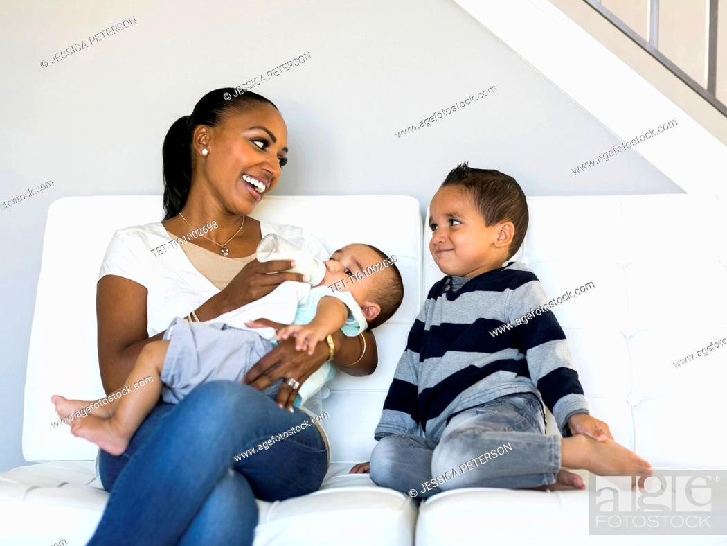 Stock Photo: Mother with two sons (2-5 months, 2-3) on sofa.