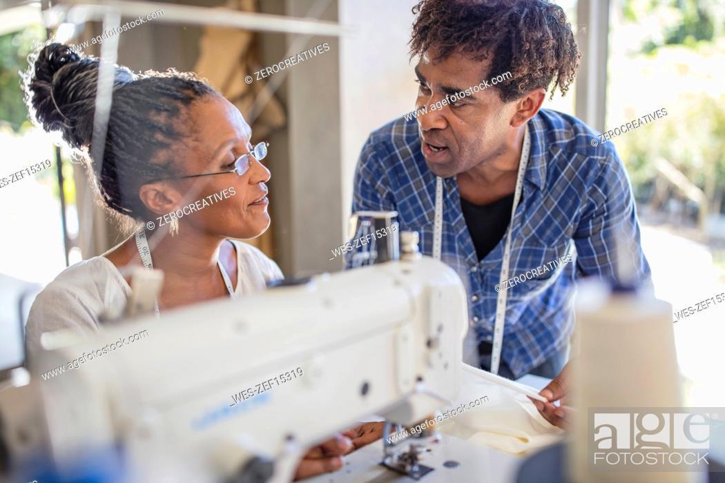Stock Photo: Fashion designer talking to seamstress in studio.