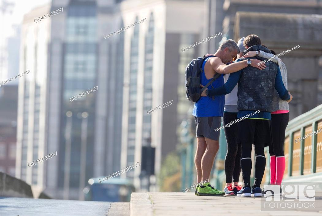 Stock Photo: Runners connected in a huddle on sunny urban sidewalk.