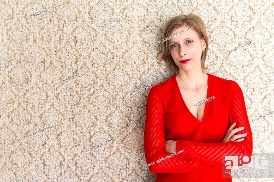 Stock Photo: Tilburg, Nethetlands. Classical Music Teacher wearing a Red Dress leaning against her vintage reading room wall.