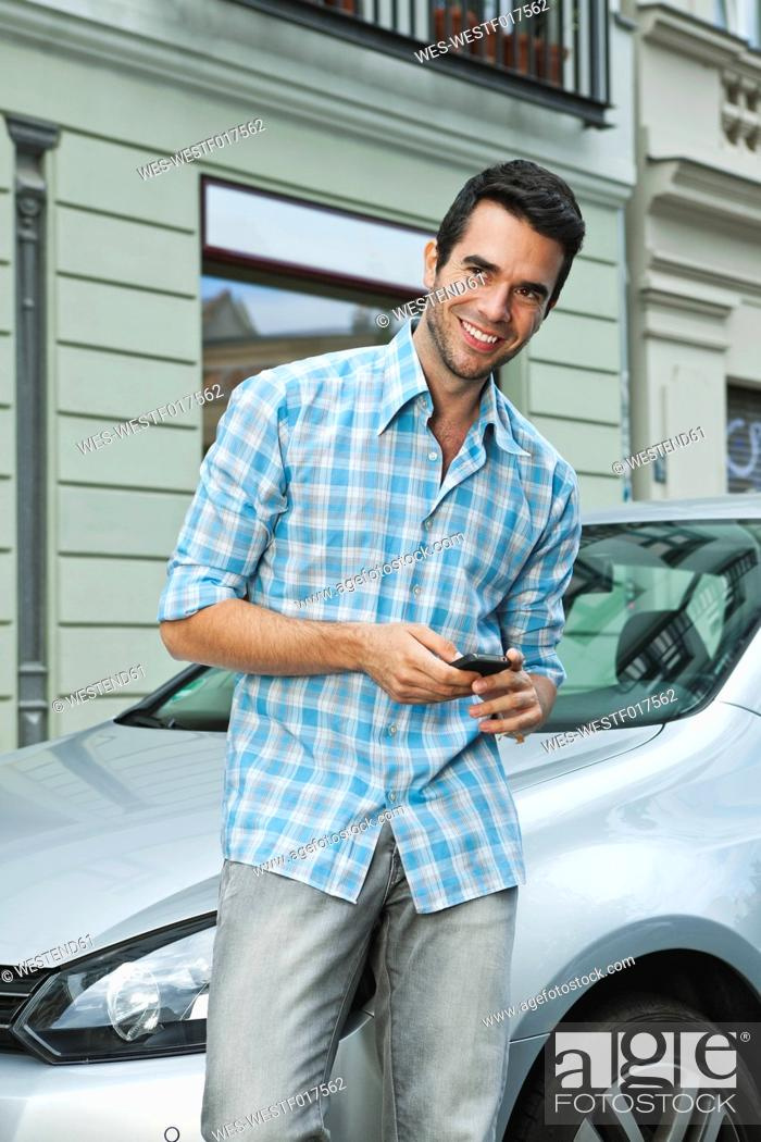 Stock Photo: Germany, Berlin, Man using cell phone in front of car.