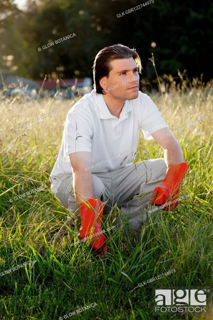 Stock Photo: Man crouching in grass.