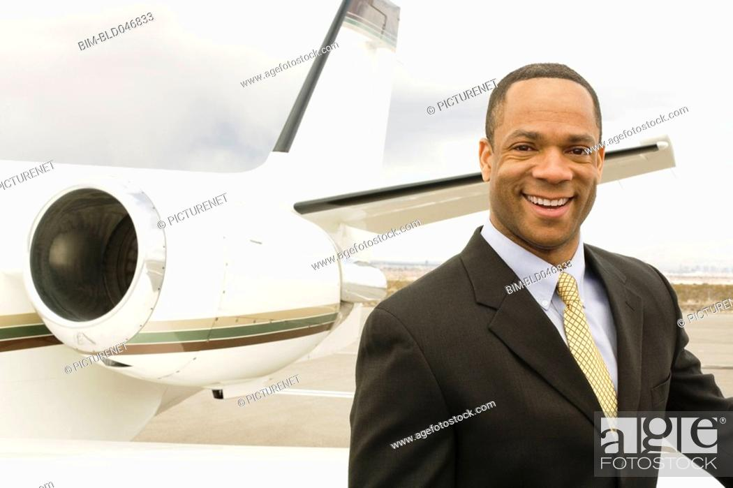 Stock Photo: African businessman next to airplane.