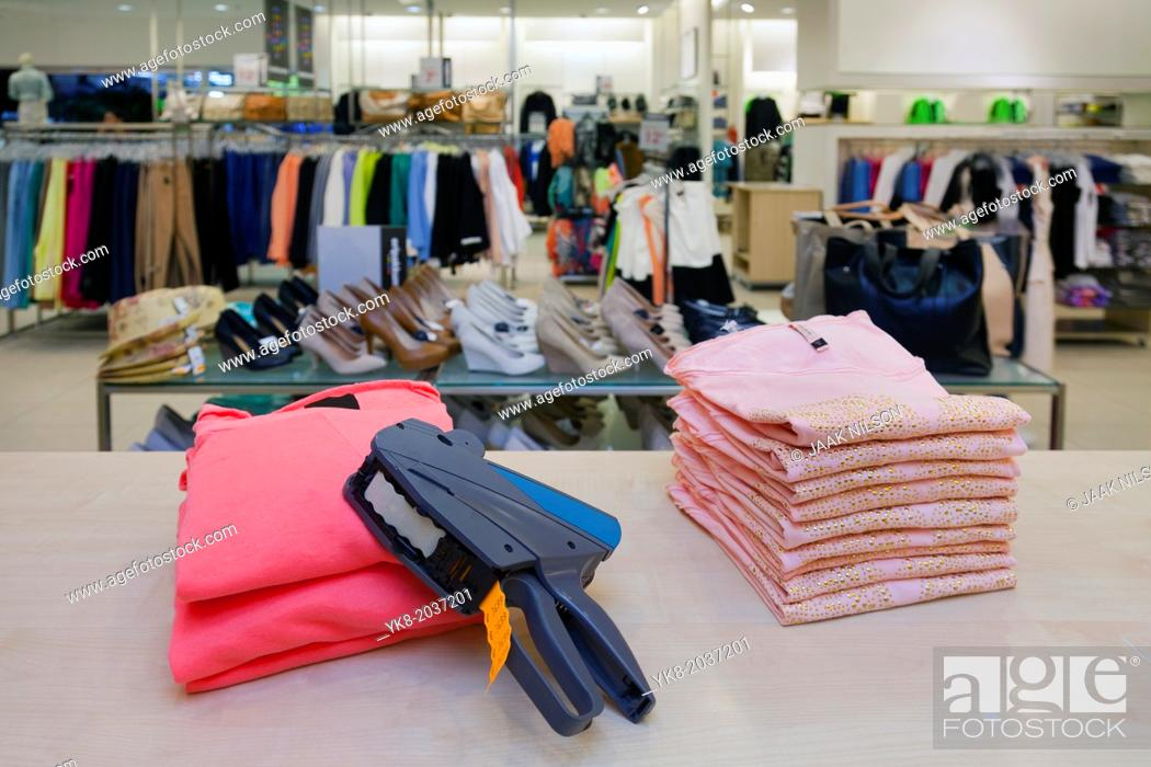 Stock Photo: Pricing, store, desk.. Price gun on folded clothes of counter in retail shop interior.