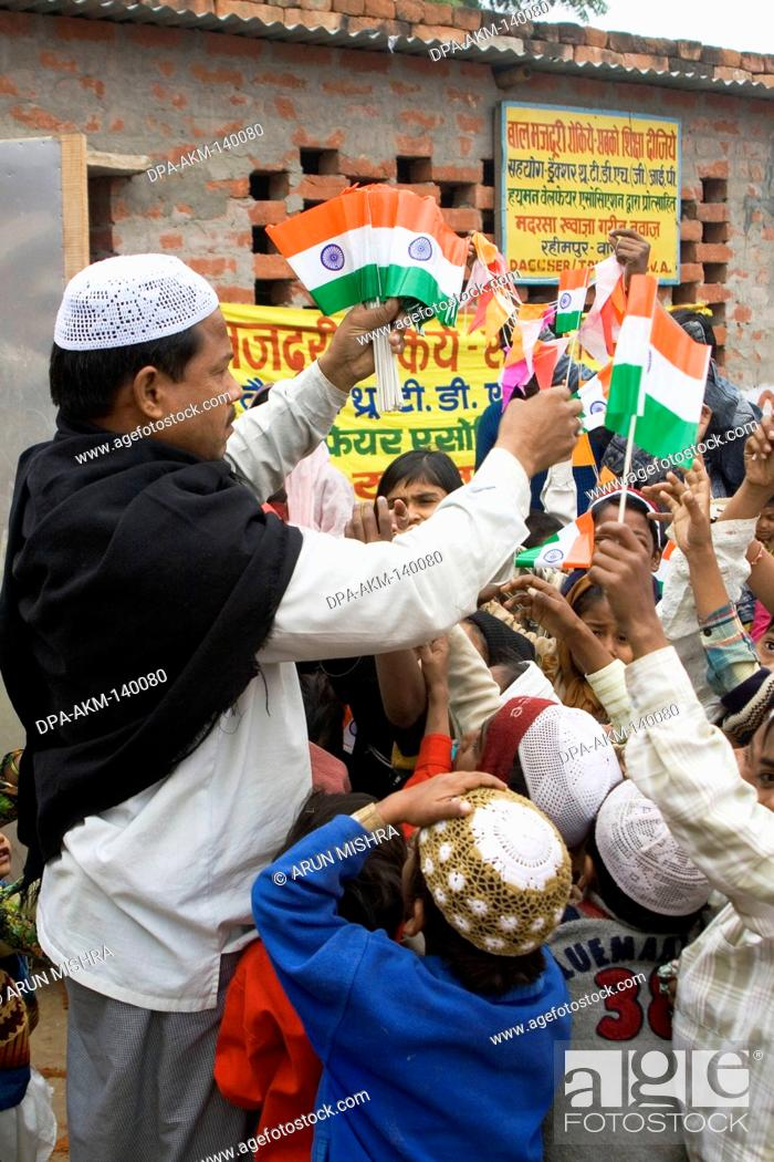 Stock Photo: Muslim man distributing Indian flag to school children on republic day 26th January in Varanasi ; Uttar Pradesh ; India.