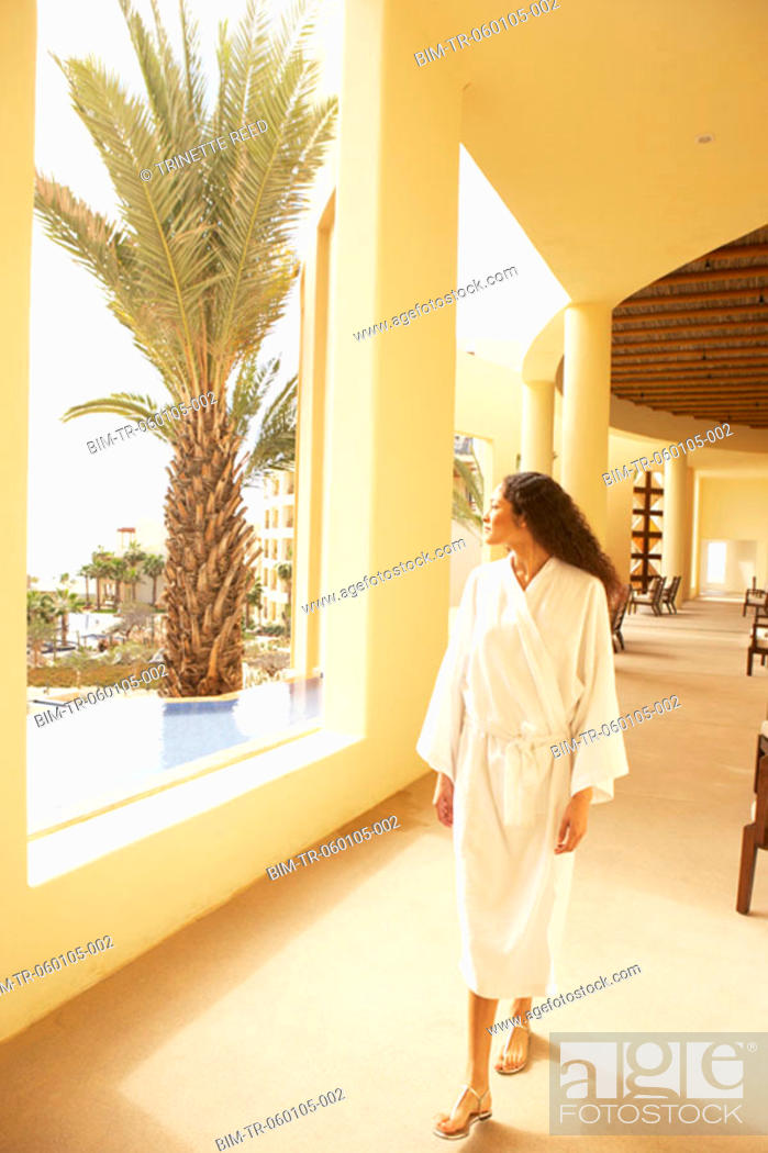 Stock Photo: Woman walking in sunlit resort hotel hallway, Los Cabos, Mexico.