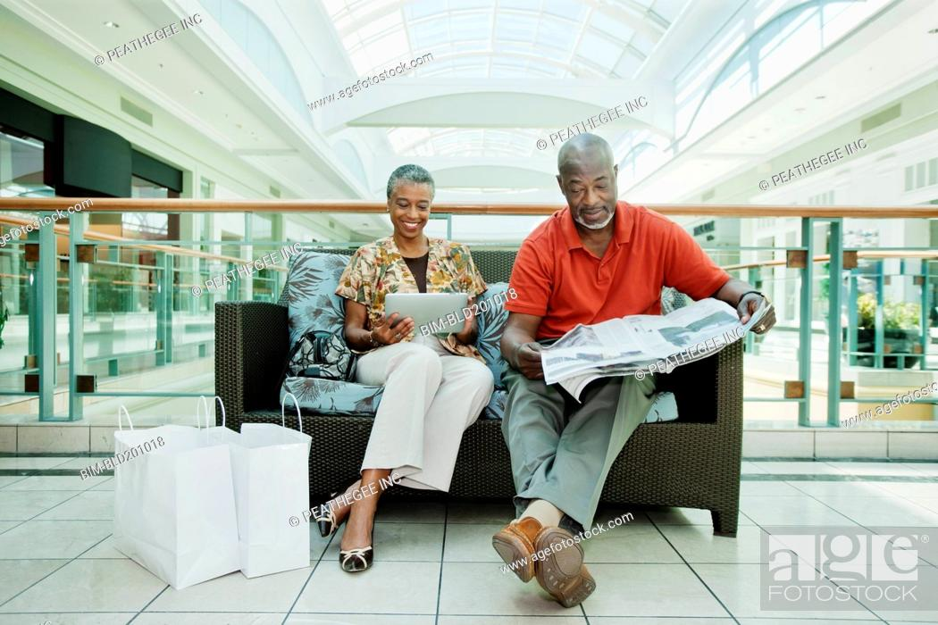 Stock Photo: Black couple relaxing on sofa in shopping mall.