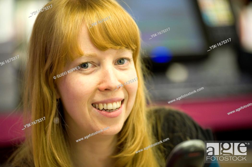Stock Photo: Rotterdam, Netherlands. Young, attractive and redheaded woman, working full of joy, in a museum bookstore.