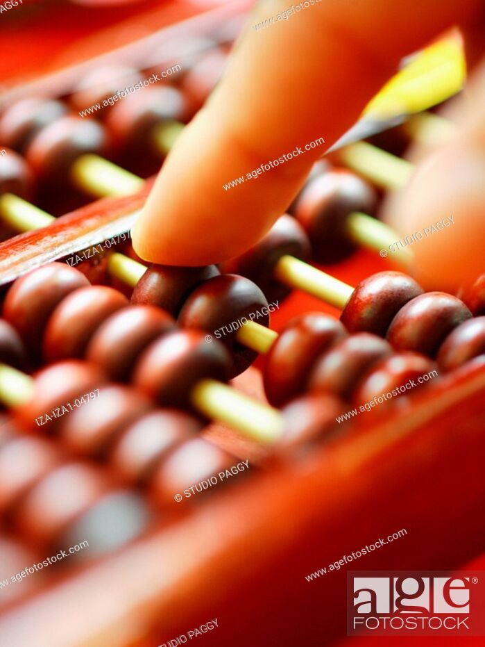 Imagen: Close-up of a person's hand using a Chinese abacus.