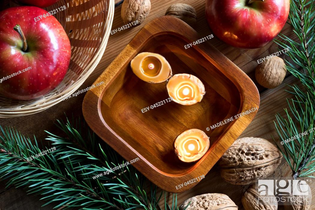 Stock Photo: Christmas decoration - apples, pine branches, walnuts and floating candles made from nutshells in a bowl of water, top view.