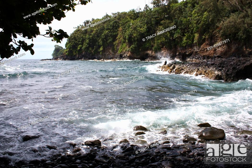 Stock Photo: Black, smooth rocks at the bottom of Donkey Trail meeting the Pacific Ocean at Onomea Bay in Papaikou, Hawaii.