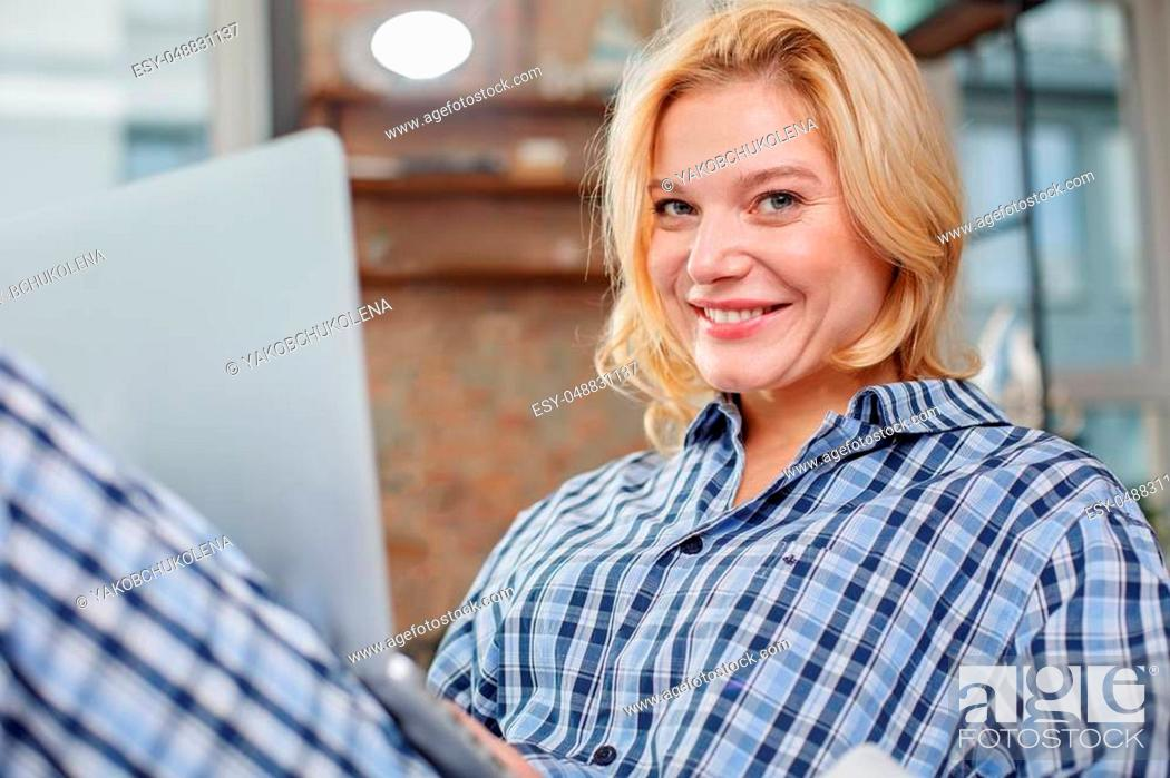 Stock Photo: Portrait of young laughing lady holding device on her knees. She is looking at camera with beautiful smile.
