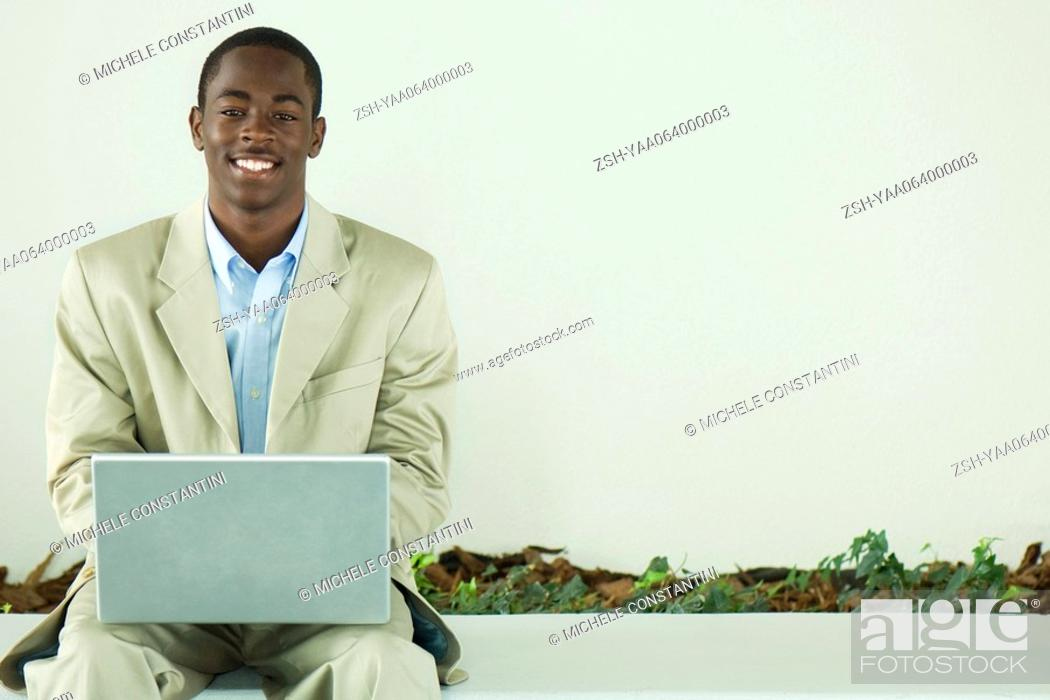 Stock Photo: Teenage boy in suit sitting, using laptop computer, smiling at camera.