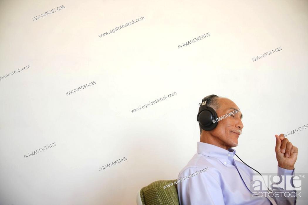 Stock Photo: Senior man listening music, side view.