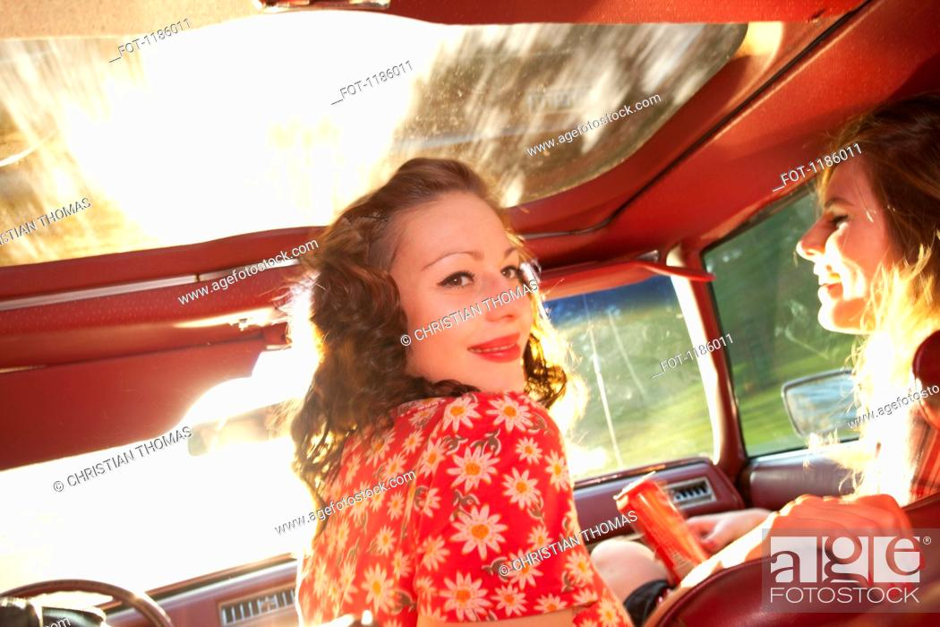 Stock Photo: Two rockabilly women having fun in the front seat of a vintage car.