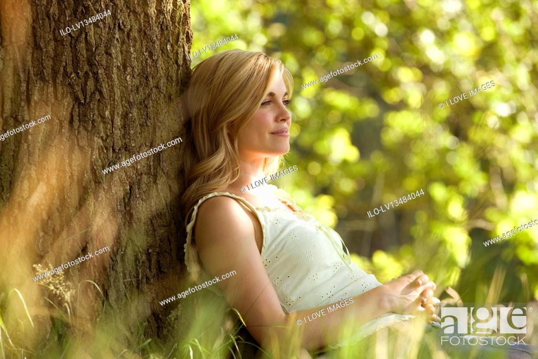Stock Photo: A young woman leaning against a tree, resting.