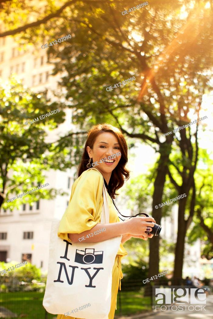 Stock Photo: Woman taking pictures in urban park.