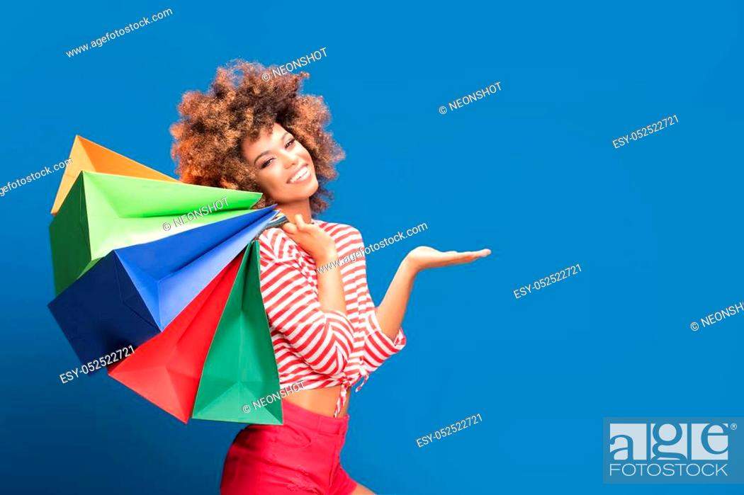 Stock Photo: Happy african american woman holding colorful shopping bags, smiling, posing on blue background. Shopaholic content.