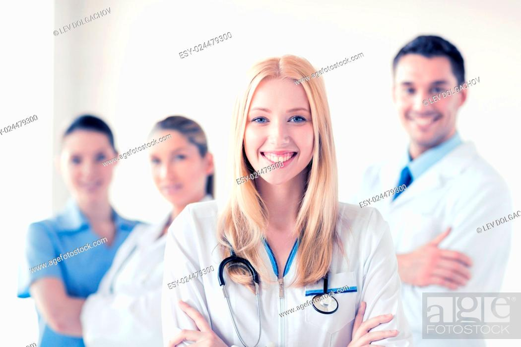 Stock Photo: attractive female doctor in front of medical group.