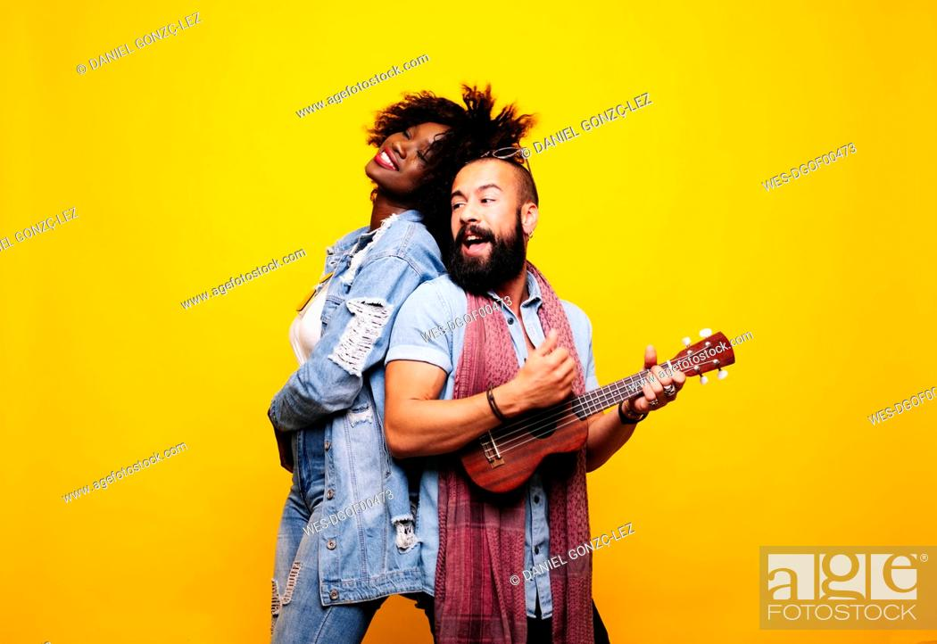 Imagen: Happy young man with woman in studio playing ukulele.