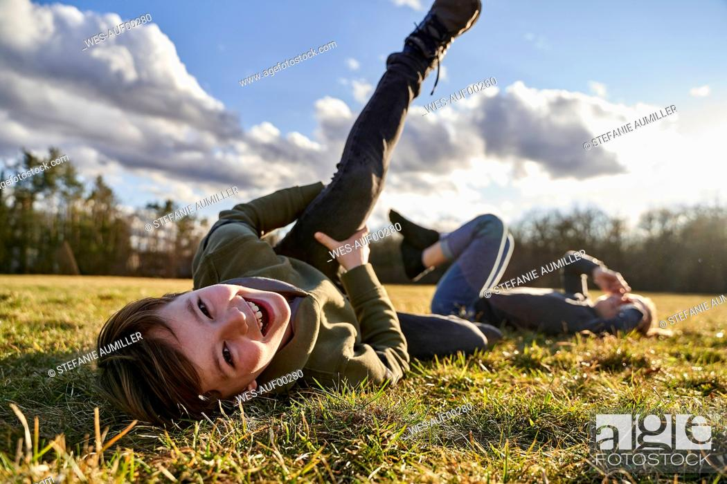 Stock Photo: Portrait of happy boy with sister lying on a meadow.