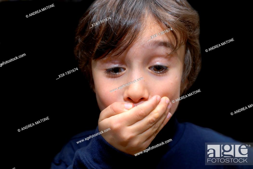 Stock Photo: Male child keeping a secret with a hand over his mouth.